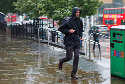 © Licensed to London News Pictures. 23/06/2016. London, UK. A man runs to take shelter from the rain in Islington, London on the polling day of the EU referendum on 23 June 2016. Photo credit: Tolga Akmen/LNP