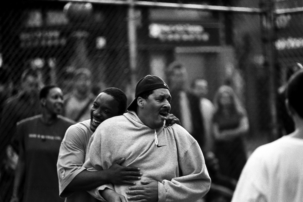October 1st 2005. New York, New York. United States..Located in the heart of Greenwich Village, the West 4th Street basketball Court, known as ?The Cage?, offers no seating but attracts the best players and a lot of spectators as soon as spring is around the corner..Half the size of a regular basketball court, it creates a fast, high level of play. The more people watch, the more intense the games get. « The Cage » is a free show. Amazing actions, insults and fights sometimes, create tensions among and inside the teams. The strongest impose their rules. Charisma is present..?The Cage? is a microcosm. It?s a meeting point for the African American street culture of New York. Often originally from Jamaica or other islands of the Caribbean, they hang out, talk, joke, laugh, comment the game, smoke? Whether they play or not, they?re here, inside ?The Cage?. Everybody knows everybody, they all greet each other, they shake hands and hug: ?Yo, whasup man??.