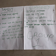 On a large piece of paper, girls from the township of Lamontville in Durban hace written how they think they should behave with their family and their community during a bahavioral change communications workshop. 09 November 2017. Lamontville, Durban, South Africa.  © Miora Rajaonary / Wall Street Journal