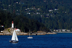 Point Atkinson Lighthouse with sailboat passing, West Vancouver, British Columbia, Canada