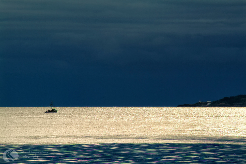 A lone fishing boat plys the waters off Quadra Island in the Straits of Georgia.