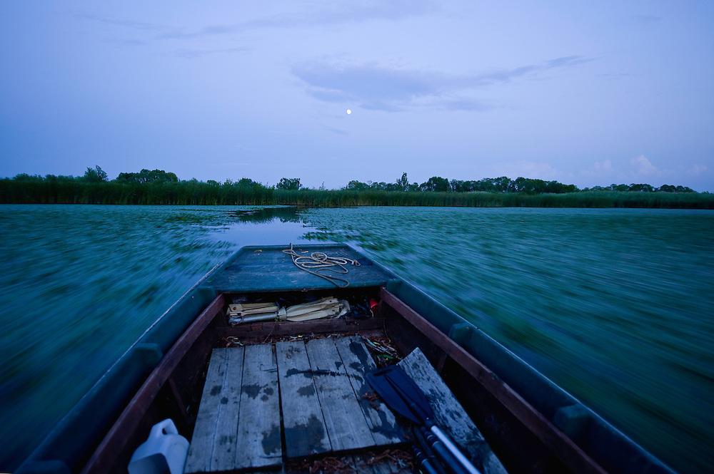 Wooden boat on Tisza lake at dusk, Hortobagy National Park, Hungary