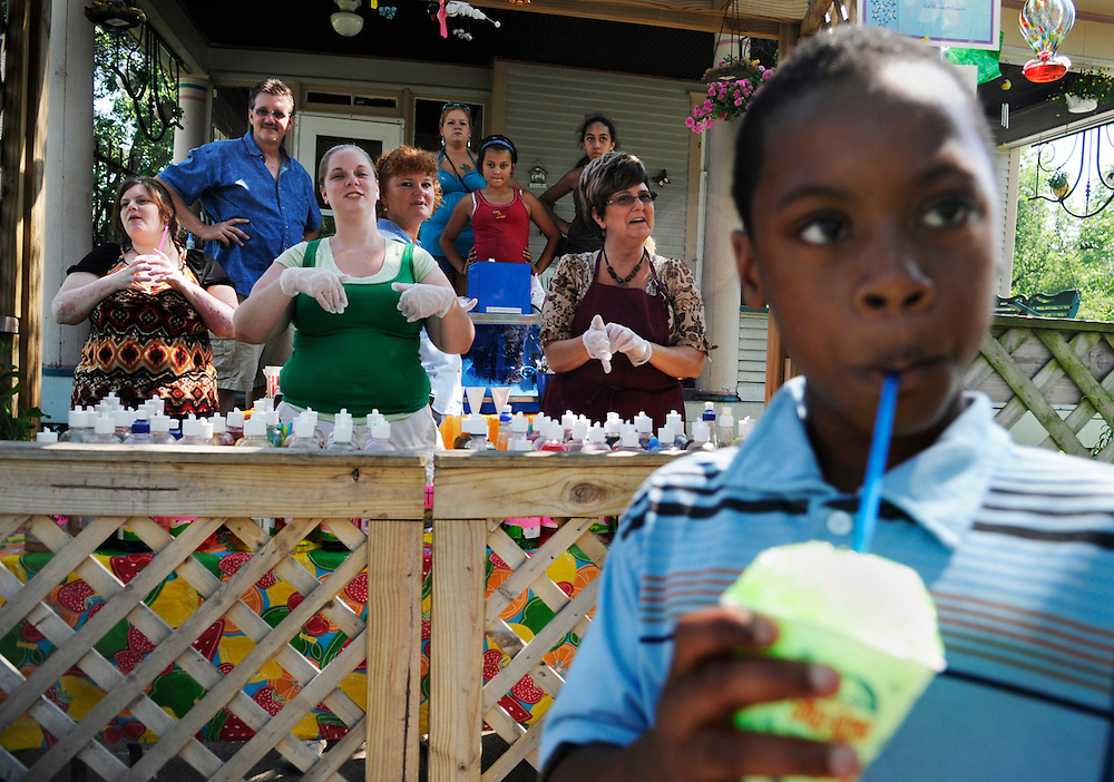 Darion Hicks, 9, of Muskegon, Mich., enjoys a free sno cone outside the home of Vickie Bromley at 205 W. Grand Ave. in Muskegon, Mich., on June 23, 2009. Bromley (background, right), with the help of her family, has been giving out free sno cones at her home each Tuesday of the summer for the past eight years. Passerby can currently choose from over 60 flavors, ranging from the traditional blue raspberry to the more adventurous dill pickle.