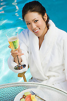 Young woman drinking champagne by swimming pool, portrait