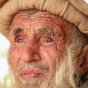 A local elder watches with sadness as the village sawmill goes up in flames, struck by a Taliban rocket-propelled grenade.