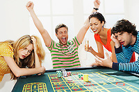Young man winning on roulette table while friends lose