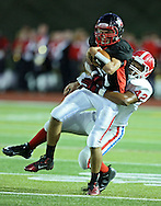 Linn-Mar's Rhys Davis (11) is pulled down by Washington's Robert Miley Jr. (42) on a run during the first quarter of the game between Cedar Rapids Washington and Linn-Mar at Linn-Mar Stadium in Marion on Friday, September 14, 2012.