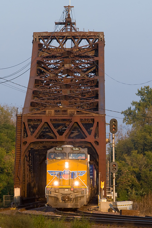 In the fading light of day, a westbound Union Pacific intermodal train rolls it's cargo bound for the Pacific ports in Los Angeles, CA off the huge and rusty swing bridge over the mighty Mississippi River into Clinton, IA.