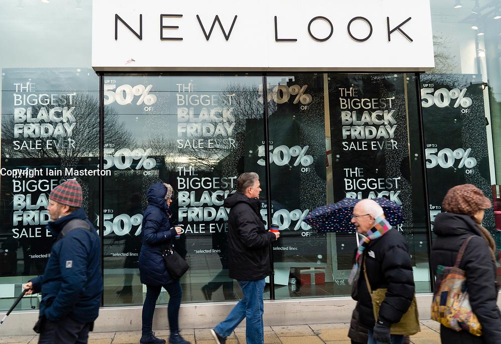 Edinburgh, Scotland, UK. 23 November, 2018. Shoppers walk past shops with Black Friday price discount promotion displays on Princes Street , Edinburgh, Scotland,