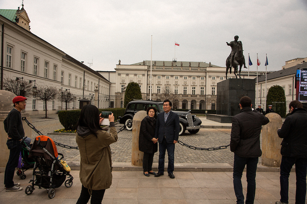 Tourists pose for photographs outside what is now the Presidential Palace in Warsaw. The building was the site of Chopin's first public performance in 1818.