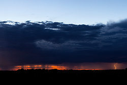 Lightning seen from 40 miles away lights up the horizon as storm clouds move over the open prairie of Central Illinois on a night which also brought out lots of fireflies in the foreground during a beautiful sunset.