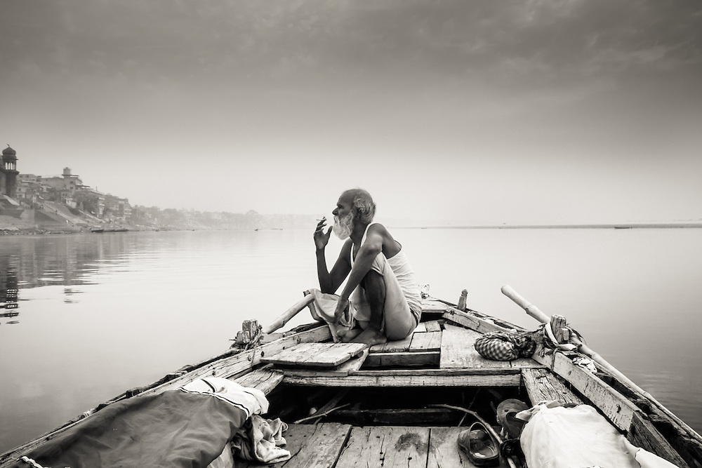 A boatsman, who calls himself Baba Boatsman, takes a cigarette break on the river Ganges at sunrise and stares at the shores of Varanasi, India.