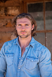 portrait of a good looking man with long brown hair and blue eyes outdoors