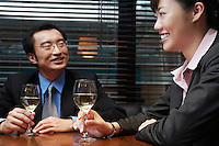Two business people holding wine glasses sitting in cafe