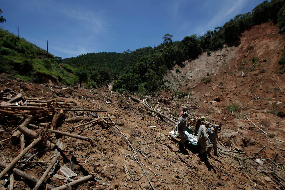 Firefighters, National force and residents recover the body of a landslide victim from a house where they found 8 family members in Nova Friburgo, Brazil, Thursday, Jan. 20, 2011. <br /> <br /> A series of flash floods and mudslides struck several cities in Rio de Janeiro State, destroying houses, roads and more. More than 900 people are reported to have been killed and over 300 remain missing in this, Brazil&rsquo;s worst-ever natural disaster.