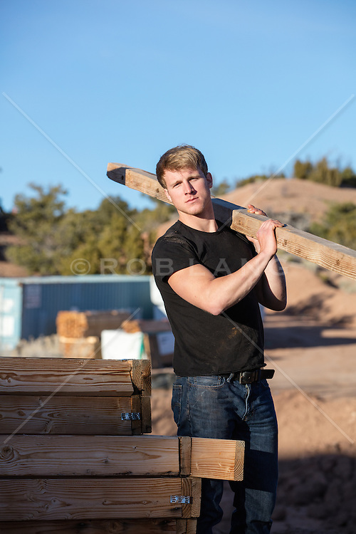 hot construction worker carrying wood on a job site