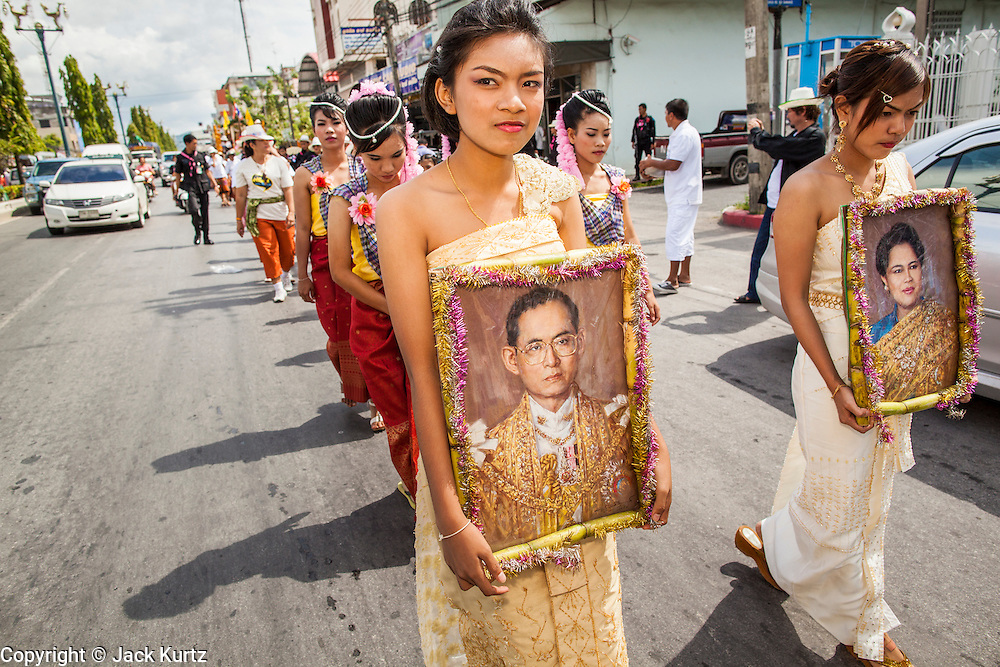 31 OCTOBER 2012 - YALA, YALA, THAILAND: Women from Wat Kohwai process through the streets of Yala for Ok Phansa. Ok Phansa marks the end of the Buddhist 'Lent' and falls on the full moon of the eleventh lunar month (October). It's a day of joyful celebration and merit-making. For the members of Wat Kohwai, in Yarang District of Pattani, it was a even more special because it was the first time in eight years they've been able to celebrate Ok Phansa. The Buddhist community is surrounded by Muslim villages and it's been too dangerous to hold the boisterous celebration because of the Muslim insurgency that is very active in this area. This the year the Thai army sent a special group of soldiers to secure the village and accompany the villagers on their procession to Yala, a city  about 20 miles away.   PHOTO BY JACK KURTZ