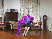 Senior woman wearing feather boa sitting on love seat in living room (portrait)