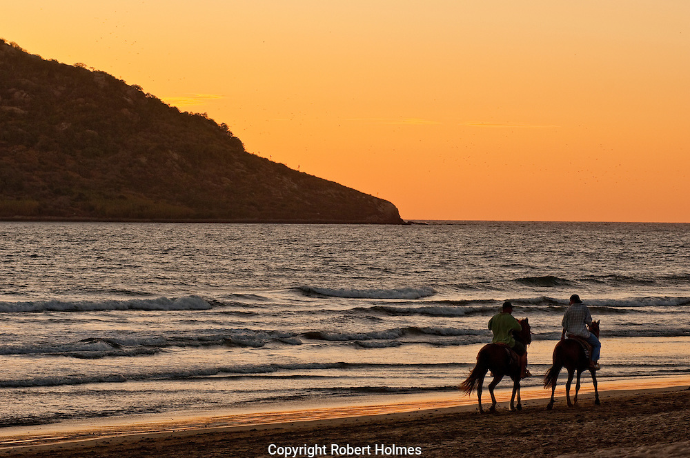 Riding horses on the beach at sunset, Mazatlan, Mexico