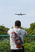 A man climbs  looks over a fence near Atsugi Airbase and watch the military aircraft. Yamato, Kanagawa, Japan. Tuesday May 1st 2018