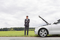 Young businessman standing arms crossed by broken down car at countryside