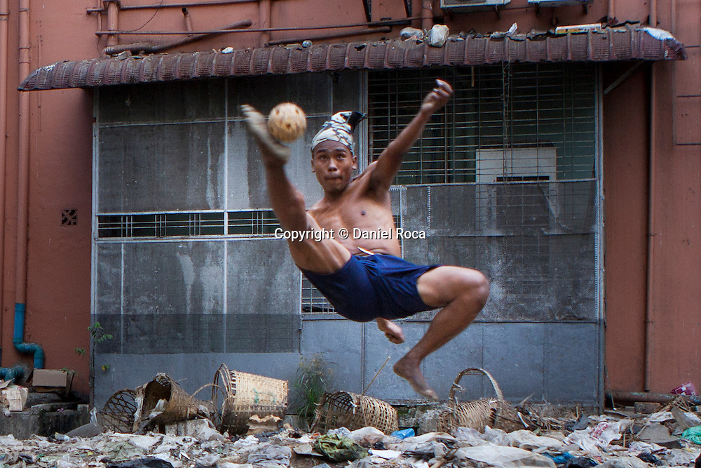 A player makes a pirouette to hit the ball. Yangon, Myanmar.