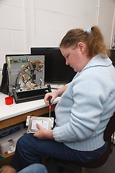 Woman with a mild learning disability working as a trainee computer technician, shown here attaching hard drive,helped into employment by the Ready 4 Work team, Nottinghamshire County Council