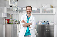 Portrait of smiling doctor standing with arms crossed at veterinary clinic