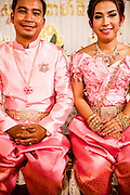 Elaborate outfits of bride and groom at Khmer wedding