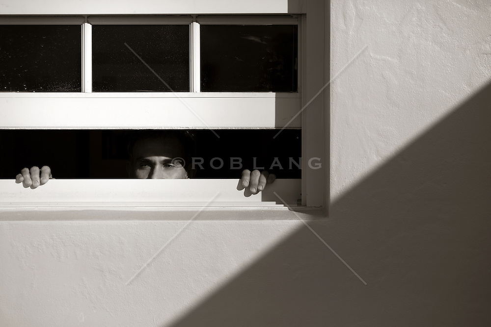 man looking out an open window