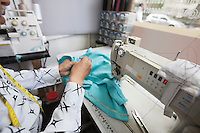 Cropped image of male tailor stitching cloth while sitting by sewing machine