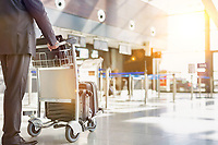 Mature businessman pushing baggage cart for check in at airport