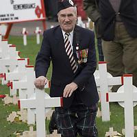 Veteran kneeling near crosses at Remembrance day ceremony in Edinburgh,<br />