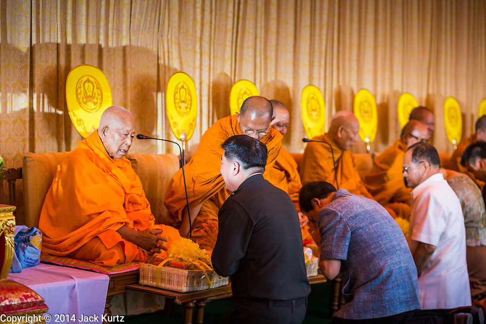 """22 JULY 2014 - BANGKOK, THAILAND:  Members of the Thai elite make merit by giving alms to Buddhist monks during a chanting service and merit making ceremony at Sanam Luang. Hundreds of Thai military officers and civil servants attended a Buddhist chanting service and merit making ceremony to mark the 2nd month anniversary of the May 22 coup that deposed the elected civilian government and ended nearly six months of sometimes violent anti-government protests. The ruling junta said the ceremonies Tuesday were the kickoff to a """"Festival to Bring Back Happiness of the People of the Nation."""" There will be free concerts, historical pageants and movies at Sanam Luang, a large parade ground near the Ministry of Defense in Bangkok.   PHOTO BY JACK KURTZ"""