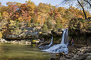 A woman approaches Upper Falls in Cataract Falls State Recreation Area –  Indiana's largest-volume waterfall. Mill Creek plunges 20 feet in the set of Upper Falls, and a half a mile downstream the Lower Falls drops 18 feet, for a total drop of 86 feet including intermediate cascades. Autumn foliage colors were brilliant but water volume was low for this photo in mid October 2015. The park's limestone outcroppings formed millions of years ago when the region was covered by a large shallow ocean. Cataract Falls State Recreation Area is an hour southwest of Indianapolis, near Cloverdale, Indiana, USA.