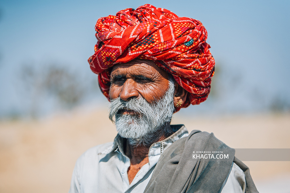 Portrait of an old ethnic Rajasthani man with white beard wearing a bright red turban and gold earings standing in the harsh winter sun.