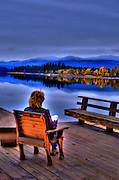 USA, Idaho, Valley County, McCall, Lake Payette, Woman reading on a Deck on the Shore of the Lake (Model Release)