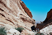 Israel, Negev desert, people hiking in the arid rock formations landscape