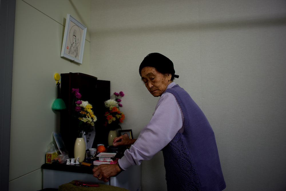 May 28, 2013 - Togura, Japan: Grandmother Abe, who become a widower when her husband died during the 2011s tsunami that struck over the coastal areas of Japan, prays at the shrine in memory of her husband in the family's pre-fabricated house. (Paulo Nunes dos Santos)