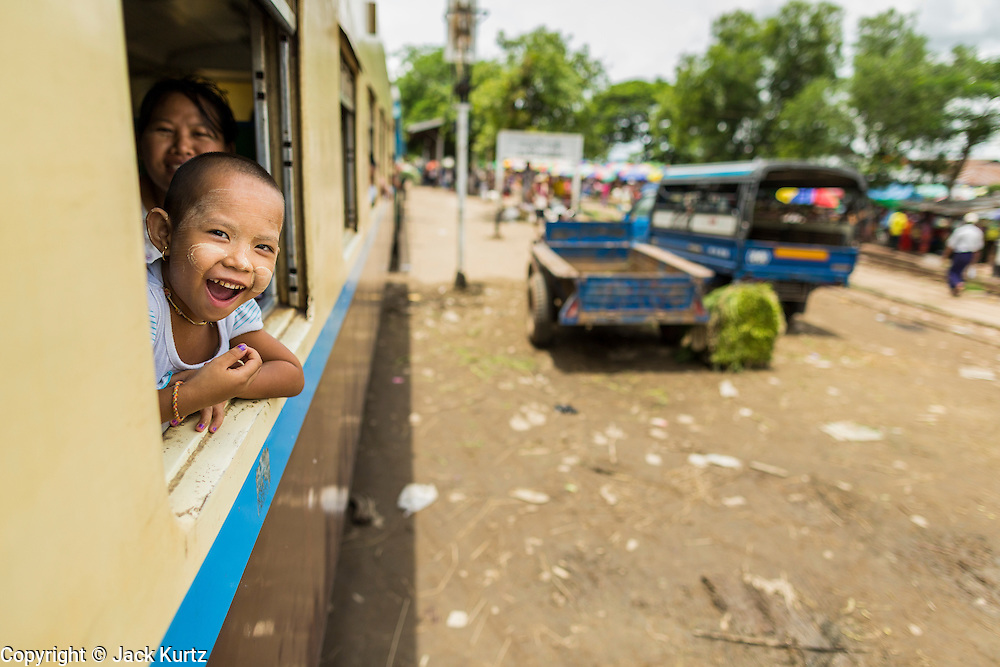 05 JUNE 2014 - YANGON, YANGON REGION, MYANMAR: A child leans out the window of the Yangon Circular Train as it rolls through the Burmese countryside. The Yangon Circular Train is a commuter train that circles Yangon, Myanmar (Rangoon, Burma). The train is 45 kilometers long, makes 38 stops and takes about three hours to make a loop of the city.     PHOTO BY JACK KURTZ