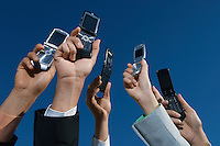 Business people holding mobile phones up in air, close-up of hands