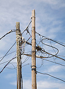 Confused tangle electricity phone line cables telegraph pole blue sky