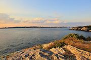 Twilight Seascape as sun begins to set on the horizon, Newport, Rhode Island. Newport Bridge is seen in the distance.
