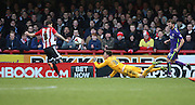 Charlton Athletic goalkeeper, Nick Pope (30) making a save from Brentford striker, Marco Djuricin (8) during the Sky Bet Championship match between Brentford and Charlton Athletic at Griffin Park, London, England on 5 March 2016. Photo by Matthew Redman.