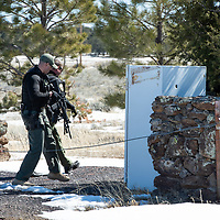 Cibola County Sheriffs Sgt. Nickolas Wadford, far, and Deputy Julian Armijo, near, cross the rope gate to the Aggressive Christianity Missions Training Corps (ACMTC) headquarters in Fence Lake Feb. 27th, 2019.