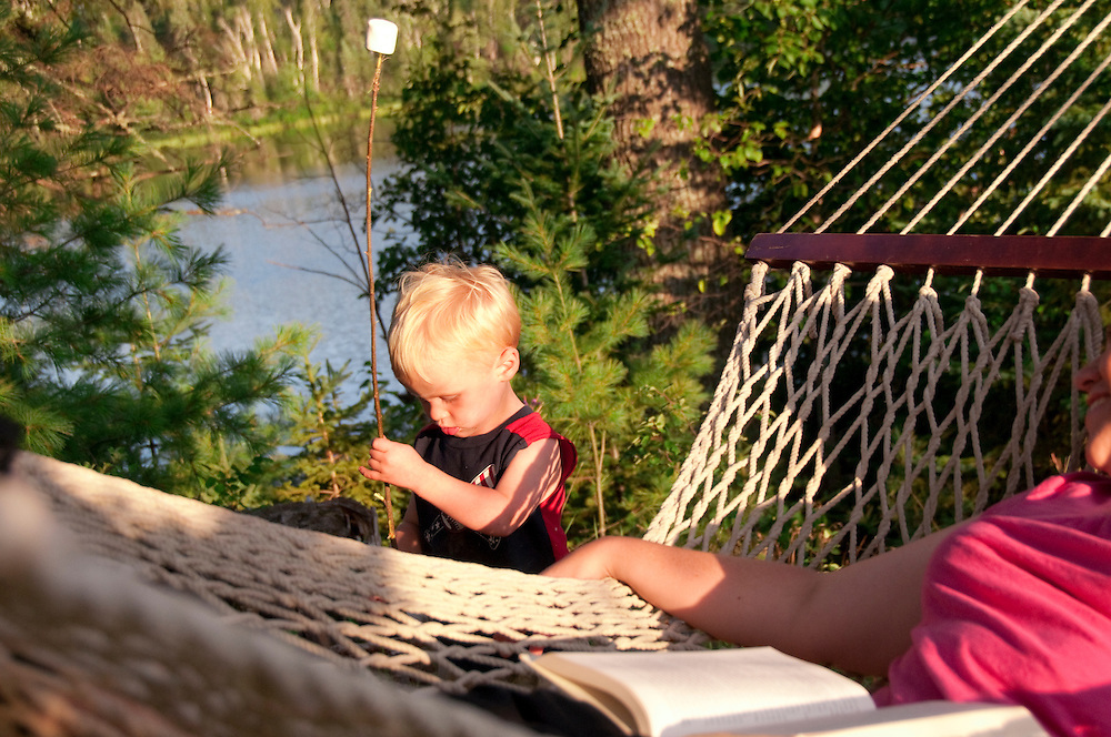 A young boy plays with a marshmallow stick while his mother relaxes in a hammock at the Republic Island Cottage near Republic Michigan.