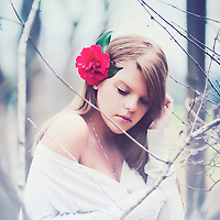 Close up of young woman with red flower in her hair outdoors in garden