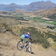 Leo Sandler from Nelson in action during the New Zealand South Island Downhill Cup Mountain Bike series held on The Remarkables face with a stunning backdrop of the Wakatipu Basin. 150 riders took part in the two day event. Queenstown, Otago, New Zealand. 9th January 2012. Photo Tim Clayton