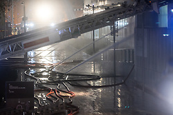 © Licensed to London News Pictures . 01/01/2018. Liverpool, UK. Fire hose jets are sprayed in to the car park . Scene at the Liverpool Echo Arena car park where firefighters are working to extinguish a fire that started late on New Year's Eve and that destroyed all 1,400 cars parked in the multi-story car park. The Liverpool International Horse Show taking place at the Arena was abandoned and people and horses evacuated as dozens of fire crew worked to control the blaze . Photo credit: Joel Goodman/LNP
