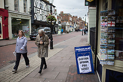 "© Licensed to London News Pictures . 17/11/2014 . Kent , UK . People walk by a local newspaper board advertising "" Election opinion poll latest "" on High Street Rochester , ahead of the Rochester and Strood by-election . Photo credit : Joel Goodman/LNP"
